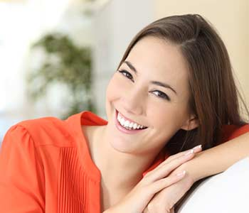 Smilling lady sitting on the chair & looking forward